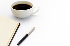 Cup of black coffee, pen and diary on white background. Minimal business concept. Flat lay. Royalty Free Stock Photos