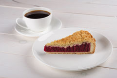 A cup of black coffee and a piece of berry pie on a plate stand on a white wooden table. A cup of black coffee and a piece of tasty berry pie on a plate stand on Stock Photography