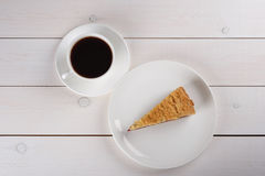 A cup of black coffee and a piece of berry pie on a plate stand on a white wooden table. Top view. A cup of black coffee and a piece of tasty berry pie on a Royalty Free Stock Photo