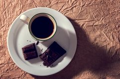 Cup of black coffee with a pieces of dark chocolate. Flat lay on brown textural paper background. stock photos