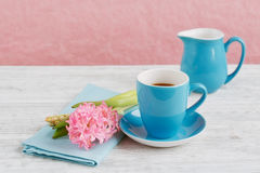 Cup of black coffee and pink flower. Cup of black coffee and pink hyacinth flower on white wooden table Royalty Free Stock Image