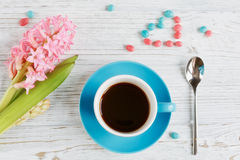 Cup of black coffee and pink flower. Cup of black coffee and pink hyacinth flower on white wooden table Royalty Free Stock Photo