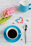 Cup of black coffee and pink flower. Cup of black coffee and pink hyacinth flower on white wooden table Stock Images