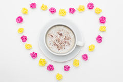 Cup of black coffee pink yellow roses laid out in the shape of a heart on a white background. Royalty Free Stock Image