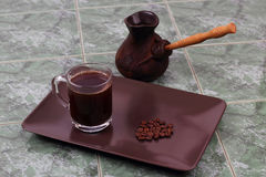 Cup of black coffee on a plate next to the vessel for brewing co Royalty Free Stock Images