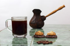 Cup of black coffee on a plate next to the vessel for brewing co Stock Photography