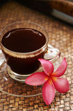 Cup of black coffee. Cup of coffee and plumeria flower in otrental style royalty free stock images