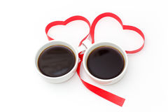Cup of black coffee with red hearts with ribbon on white background. Stock Photography