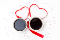 Cup of black coffee and a red ribbon in the shape of hearts on a white background with pink sprinkles. Royalty Free Stock Photos