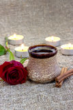 Cup of black coffee with red rose and candles. Cup of black coffee with coffee beans, red rose, candles, on sackcloth Royalty Free Stock Images