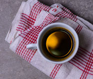 A cup of black coffee on a red white table cloth Royalty Free Stock Photos