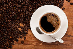 Cup of black coffee with roasted coffe beans Stock Images