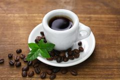A cup of black coffee with roasted coffee beans and leaves stock images