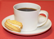 Cup of Black Coffee on Saucer with Biscuit. A cup of black coffee on a saucer with half a yoyo biscuit set against a red background Royalty Free Stock Photo