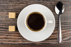Cup of black coffee on saucer, lumpy sugar and spoon Royalty Free Stock Photos