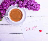 Cup of black coffee and a saucer and white paper envelope Stock Images