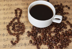 Cup of black coffee on sheet music with cinnamon and beans Stock Images