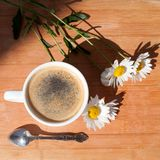 A cup of black coffee, silver spoon, branch of white daisy flowers on wooden background top view royalty free stock photo