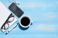 Cup of black coffee and smart phone with office supplies; pen, notebook and eyes glasses on blue wooden table background royalty free stock photography