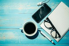 Cup of black coffee and smart phone with office supplies; pen, notebook and eyes glasses on wooden table background. Cup of black coffee and smart phone with stock photo