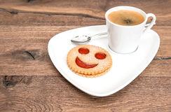 Cup of black coffee with smiled cookie. Funny breakfast Royalty Free Stock Photo