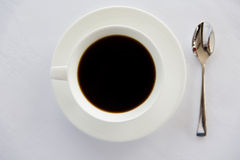 Cup of black coffee with spoon and saucer on table Royalty Free Stock Images