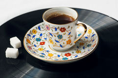 Cup of black coffee on surface of music vinil plate. Sound of morning. Stock Image