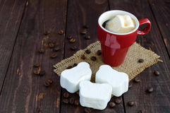 A cup of black coffee  and sweet marshmallow on a dark wooden background. Stock Images