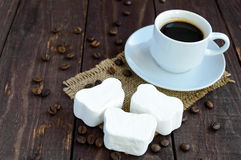 A cup of black coffee  and sweet marshmallow on a dark wooden background. Royalty Free Stock Images
