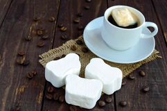 A cup of black coffee  and sweet marshmallow on a dark wooden background Stock Image