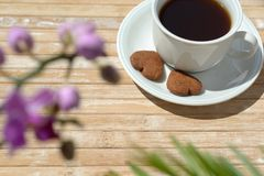 Cup coffee Heart-shaped cookies Orchids Palm leaf. A cup of black coffee with two chocolate heart-shaped cookies in its saucer. Blurred orchid flowers and palm stock image