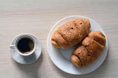 Cup of black coffee with two croissants Royalty Free Stock Photo