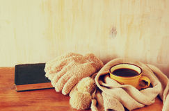 Cup of black coffee with  a warm scarf and old book on wooden background. filreted image Royalty Free Stock Photography