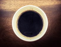 A cup of black coffee. Black coffee in white paper cup on Stock Photography