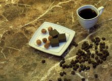 A cup of black coffee in a white porcelain cup, chocolates on a saucer and coffee beans are on a table made of beige marble. Close stock photo
