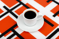 Cup with black drink inside on a black and white and red backgro. View of a cup with black drink inside on a black and white and red background Stock Photos