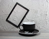 Cup black empty with an inscription mood and a photoframe. On a wall Royalty Free Stock Photos