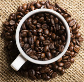 A cup of black roasted arabica coffee beans. Image of a cup of black roasted arabica coffee beans Stock Photos