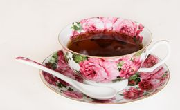 Cup with black tea. Beautiful porcelain cup with black tea on a light background royalty free stock photo