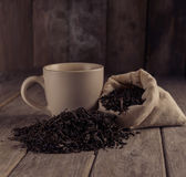 Cup of black tea. Next to a black leaf tea on a wooden table royalty free stock images