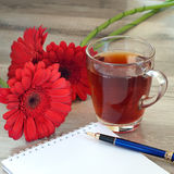 Cup of black tea with beautiful flowers gerbera and notepad Royalty Free Stock Image