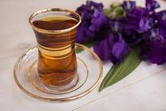 Cup of black tea and blue iris flowers Stock Photos