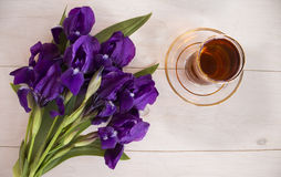Cup of black tea and blue iris flowers Stock Image