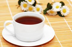 Cup of black tea and camomiles Royalty Free Stock Photography