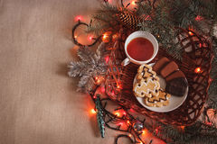 Cup of black tea and chocolate chip cookies with fir-tree branches with Christmas garland. Cup of  tea and chocolate chip cookies with fir-tree branches with Stock Photos