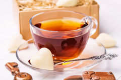 Cup of black tea with chocolates in the shape of a heart Stock Image