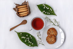 Cup of black tea in a circle of flowers of Lily of the valley, oat and almond cookies on white background Royalty Free Stock Photo