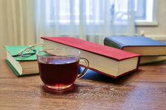 Cup of black tea and a few books on the table Stock Images