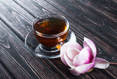Cup of black tea and flower magnolia on wooden boards. royalty free stock images