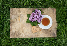 A cup of black tea and flowers of fragrant lilacs on an old wooden board. Tea in the garden. Stock Photography